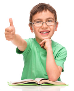 Cute little girl is reading a book and showing thumb up sign, is